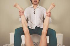 Happy man spreading legs of woman - stock photo