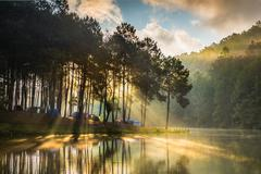 Tents on a tree lined river bank, Pang Ung, Thailand - stock photo