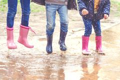 Low section of three children in wellington boots jumping in a puddle - stock photo