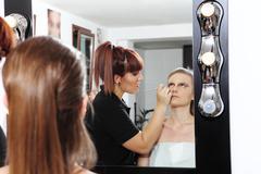makeup artist applying mascara on eyes of model - stock photo