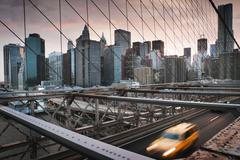 Yellow cab driving across Brooklyn Bridge at sunset, New York, USA - stock photo