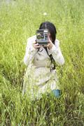 Woman taking a photo with a vintage instant camera - stock photo