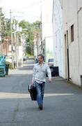 Man With Guitar Case Walking Down Alley, Port Angeles, Washington, USA - stock photo
