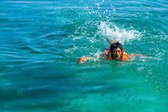 Teenage boy wearing a life jacket swimming in the sea, Salakan Island, Semporna, Stock Photos