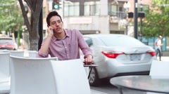 A young man sitting outside talking on his phone - stock footage