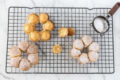 Hazelnut madeleines with caramel sauce on a cooling rack - stock photo