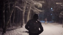 Man walks down the street during a snowy weather Stock Footage