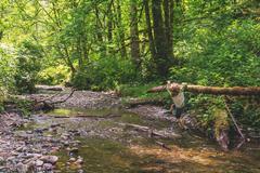 Boy hanging on fallen tree across small river Stock Photos