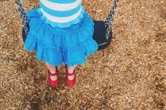 Elevated view of a girl sitting on a swing - stock photo