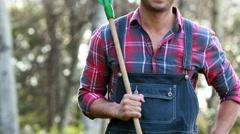 Happy farmer holding rake Stock Footage