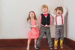 Three children in fancy dress messing about Stock Photos