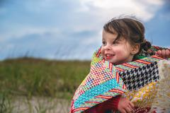 Smiling girl wrapped in a blanket outdoors Stock Photos