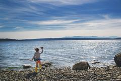 Girl throwing a rock into the sea on a windy day Stock Photos