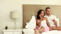 Couple laying on the bed zapping Stock Footage
