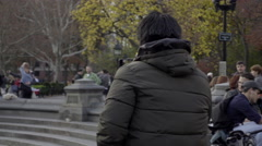 Asian man photographing himself selfie-stick in Washington Square Park NYC 4K Stock Footage