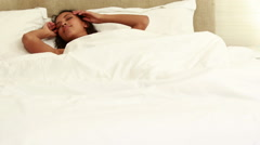 Smiling woman stretching on bed Stock Footage