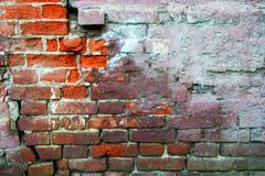 Red brick wall half covered with concrete, frame for design. Half painted wall Stock Photos
