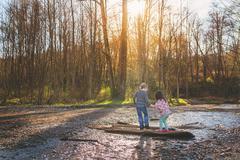 Boy helping girl walk across a log Stock Photos