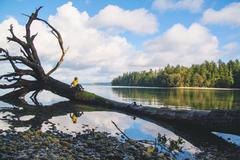 Portrait of a Boy sitting on a fallen tree in lake Stock Photos