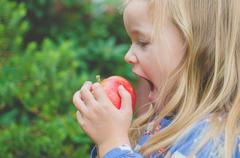 Side view of a girl about to take a bite out of an apple - stock photo