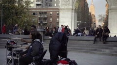Asian couple hanging out in center of Washington Square Park musicians NYC Stock Footage