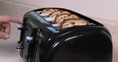 Medium shot of toast in a toaster, going down and popping up, real time in 4K - stock footage