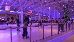 People skate on the ice rink at New Year's background Christmas tree - stock footage