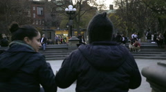 Friends hanging out near fountain center Washington Square Park slow motion NYC Stock Footage
