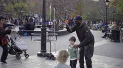 Black man and white child in racial harmony in Washington Square Park NYC Stock Footage