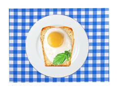Scrambled eggs with bread on plate, on color napkin - stock photo