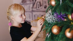 Little girl decorates the Christmas tree Stock Footage