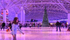 People skate on the ice rink at New Year's background Christmas tree Stock Footage