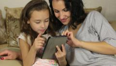 Mother and daughter playing with electronic tablet - stock footage