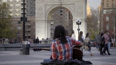 Musician playing guitar with arch in background in Washington Square Park in 4K Stock Footage