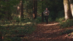 Man Jogging Toward Camera in Forest with Fall Leaves on Trail Caucasian Male Stock Footage