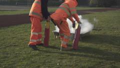 Two people putting out a fire with fire extinguishers. Stock Footage
