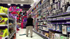 Woman wiping floor with mop inside party store - stock footage