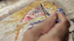 Painting an eye with a small brush on a portrait Stock Footage