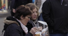 Shopping street Germany two women eating frites  Stock Footage