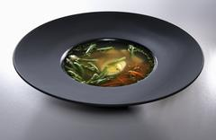 Chicken bouillon in black plate isolated on white background - stock photo