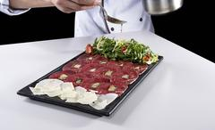 Meat carpaccio seasoned with olive oil by chief Stock Photos