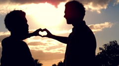 Silhouette of homosexual couple doing heart with hands together Stock Footage