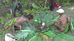 PNG  natives using hot stones over the covered food - stock footage
