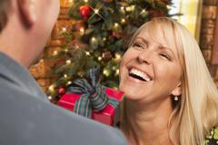 Attractive Girl Exchanging A Gift At A Christmas Party. - stock photo
