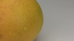 Extreme closeup orange grapefruit  in drops of dew rotates on its axis - stock footage