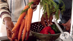Couple with apron washing vegetables Stock Footage