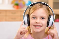 Vivacious little girl listening to music - stock photo