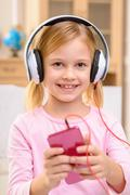 Stock Photo of Vivacious little girl listening to music
