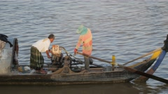 Men starting engine on fisher boat,Phnom Penh,Cambodia Stock Footage