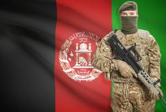 Soldier holding machine gun with national flag on background - Afghanistan - stock photo